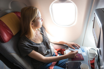 Relaxed casual woman flying on commercial passengers airplane, filling in immigration form, drinking coffee, listening to music.
