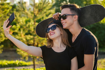 active couple in love hugging in the summer park. beautiful woman in a cap and sunglasses is holding a skateboard(longboard) and photographed take pictures selfie on phone with man . guy and girl date
