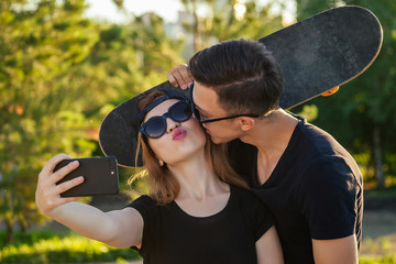 active couple in love hugging in the summer park . beautiful woman in a cap and sunglasses is holding a skateboard( longboard) and photographed take pictures selfie on phone with man . guy kisses girl