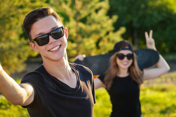 cool guy and a lovely girl in sunglasses, jeans and a black T-shirt skateboarding holding hands photographed take pictures selfie on phone in the summer park
