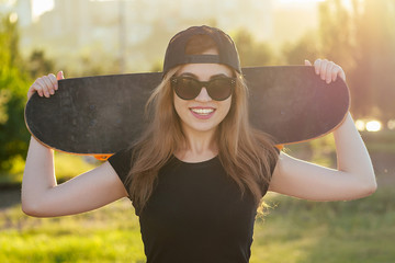 young cool girl holding a skateboard in a skatepark