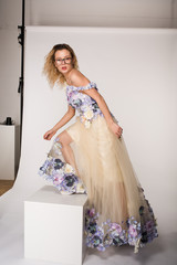 Studio portrait of blooming gorgeous lady in dress of flowers. Fashion concept