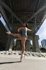 Female urban dancer dancing below the bridge