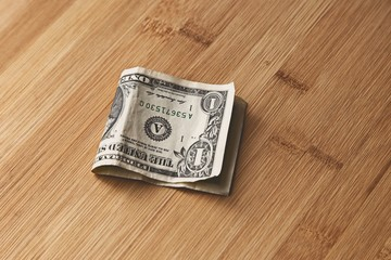 A picture of a USA dollar note on a table top. This image can be used to represent money.