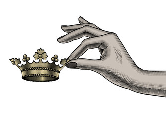 Female hand holding in fingers a gold crown