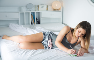Young woman is relaxing in bed and making schedule on bed