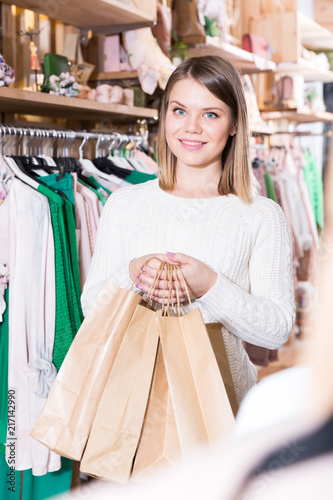 87fe1a7fc5a3c Young woman with paper bags in clothes fashion shop