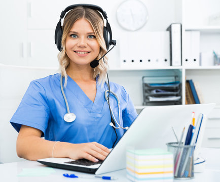 Attentive specialist of medical call center in headphones in office