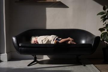 Baby girl sleeping on sofa in living room
