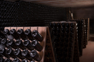 Wine bottles on racks in winery cellar