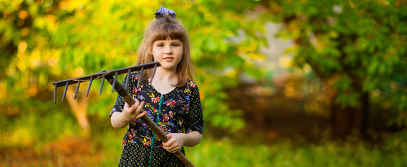 Happy little girl help parents in garden with rake. Seasonal garden work. Backyard cleaning