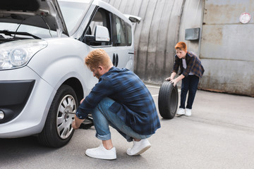 father changing tire in car with wheel wrench, son holding tire