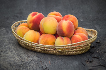 Fresh peaches in wicker basket on dark wood background
