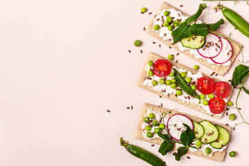 Healthy sandwiches with soft cheese and raw vegetables on crisp bread