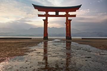 torii of Itsukushima shrine with low tide at sunset