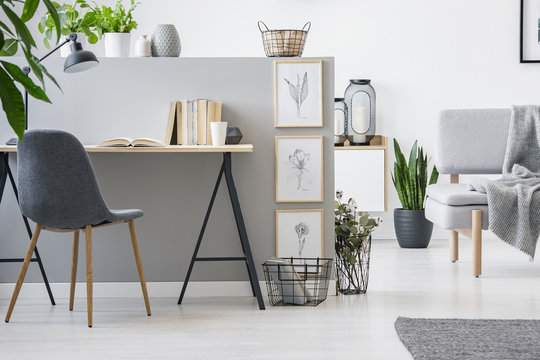Modern chair with wooden legs by an industrial desk with books by a gray wall with framed sketches in a scandianvian living room interior