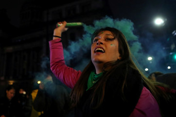 An abortion rights activist holds a flare outside the Congress after senators rejected a bill to legalize abortion, in Buenos Aires