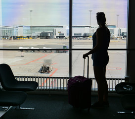 SILHOUETTE: Young woman stands by the window and looks at the airport runway.