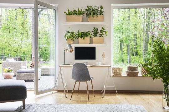 Inspirational workspace interior for a freelancer with computer on a wooden desk, white walls and the view of nature in the backyard outside