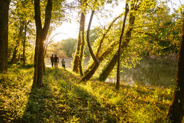 Three men stand on a riverbank campsite at dawn