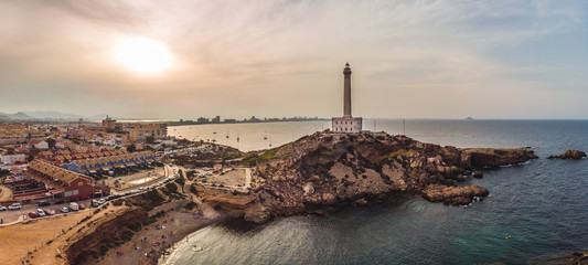 Lighthouse of Cabo de Palos, cape in the Spanish municipality of Cartagena, in the region of Murcia. Small range of volcanic mounts that form small peninsula, drone arial panoramic photo. Summer 2018