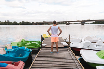 Near river. Good-looking muscle man wearing white shirt and orange shorts standing near river