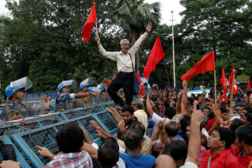 Activists of CITU break a police barricade during a protest in Kolkata