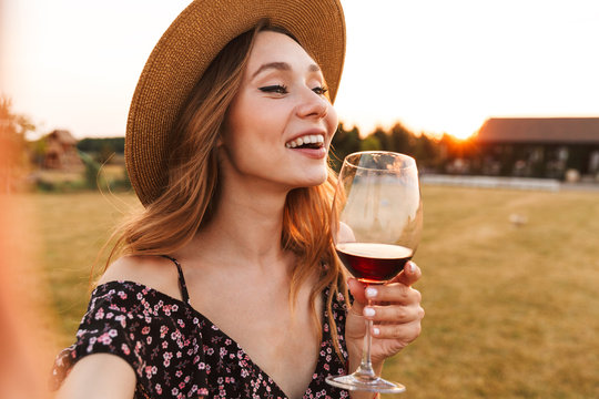 Woman outdoors holding glass drinking wine.