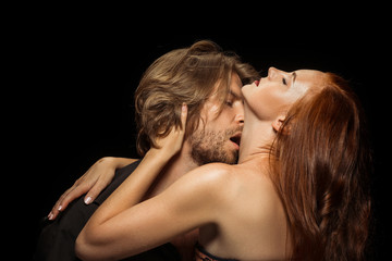 Real passion. Beautiful young loving couple bonding to each other while both standing against black background. Passion, couple, love, sensuality, erotic, sex, relationship concept