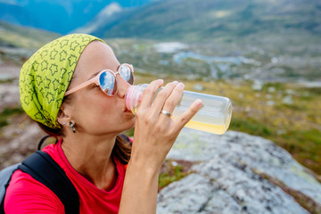 Beautiful young woman hiker in bandana and eyeglasses drinking water while going at mountain peak in Norway when hiking.