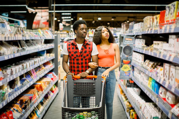 Smiling african american couple in casual clothes with shopping basket choosing wine in supermarket