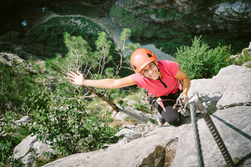 Young happy woman who is climbing along a via ferrata
