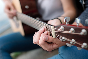 Guitar strings. Close up of a music instrument being in hands of a nice young woman while playing music