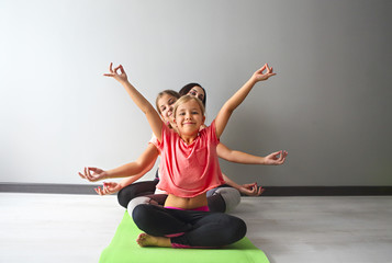 Young woman having fun with kids doing yoga