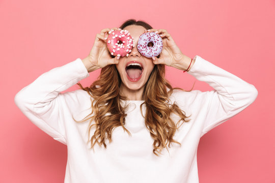 Portrait of a happy young woman showing donuts