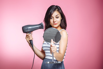 Beautiful woman using a hair dryer and smiling while looking at the mirror on a pink background.