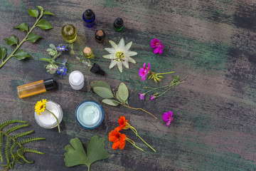Herbal cosmetic ingredients top view wooden background. Mix of flowers , herb,oil, aroma dropper essential oil bottle,on old brown black wooden background. top view