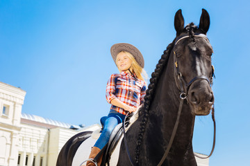 Dark horse. Smiling blonde-haired girl wearing blue jeans and riding boots sitting on dark horse