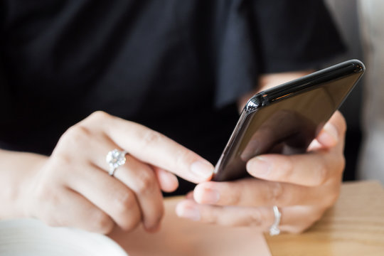 Woman with diamond ring on hand using smartphone in cafe restaurant