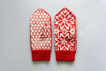 Knitted Norwegian jacquard gloves on gray wooden background. Top view. Flat lay