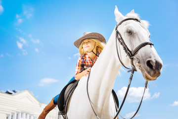 Blonde-haired girl. Blonde-haired cowboy girl wearing jeans and riding boots leaning on her racing horse