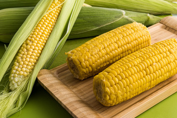 Fresh corn on the cob with leaves and boiled corn in wooden tray on green background