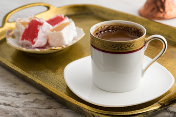 Vintage cup of turkish coffee and turkish delights served in bronze tray on marble