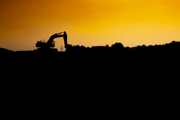 Silhouette of a excavator in the sunset