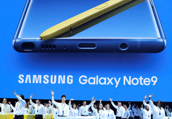 Samsung employees wave from stage beneath an image of the new Samsung Galaxy Note 9 during a product launch event in Brooklyn