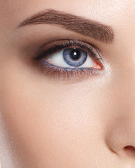 Close up of blue woman eye with beautiful brown with red and orange shades smokey eyes makeup. Modern fashion make up. Good vision, contact lenses, brow bar or fashion eyebrow makeup concept