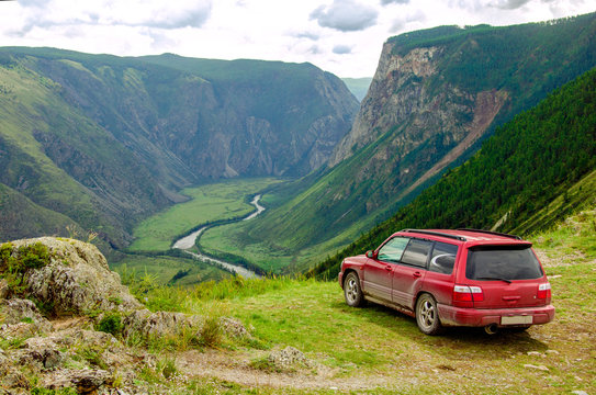 A dirty, red car is on a pass in the mountains.