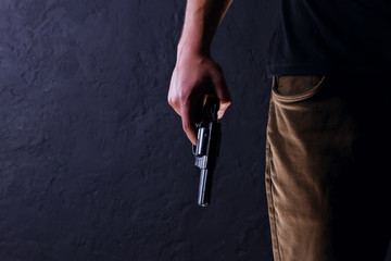 Killer with gun close up on a black background. Wall mural