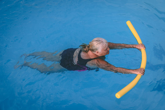 A senior female woman holds on to a flotation device on a swimming pool to learn how to swim