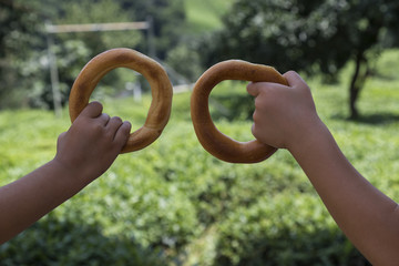 child hold the regional bagels on the green view for healthy concept.